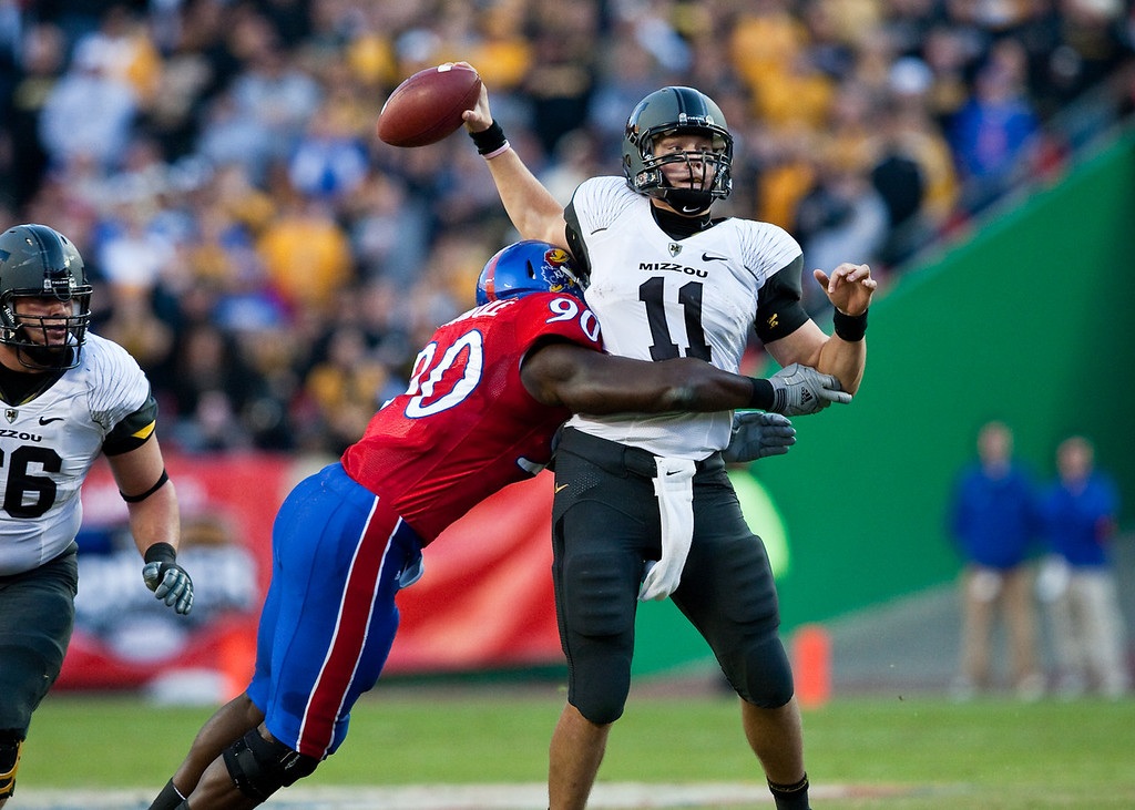 28 November 2009: Kansas defensive end Maxwell Onyegbule (90) hits Missouri quarterback Blaine Gabbert (11) and creates a fumble during the Missouri Tigers 41-39 win over the Kansas Jayhawks at Arrowhead Stadium in Kansas City, Missouri.