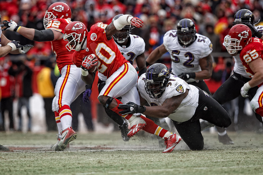 January 9, 2011: Kansas City Chiefs running back Thomas Jones (20) is tripped up by Baltimore Ravens defensive tackle Brandon McKinney (91) during an AFC Wild Card game between the Baltimore Ravens and the Kansas City Chiefs at Arrowhead Stadium in Kansas City, Missouri.