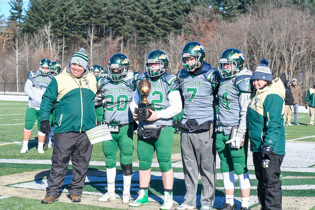 . From left, head coach Jamie Tucker accepts the Thanksgiving Day Trophy with his senior captains: Brendan Lee, , Matt Johnson, Sam Bolinsky and Matt Johnson. Also pictured is Nashoba athletic director Tania Rich. Nashoba won the contest, 21-0, in Bolton on Thanksgiving Day, Thursday, Nov. 22, 2018. Sentinel & Enterprise/Ed Niser