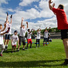 Former Patriots player Ilia Jarastchuk demonstrates a drill with kids during the New England Patriots Alumni Club's annual Football For You youth football clinic at Crocker Field on Thursday. SENTINEL & ENTERPRISE / Ashley Green