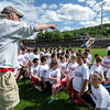New England Patriots Alumni President and former Patriots player Pete Brock talks to the kids before the start of the New England Patriots Alumni Club's annual Football For You youth football clinic at Crocker Field on Thursday. SENTINEL & ENTERPRISE / Ashley Green