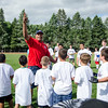 Former Patriots player Derrick Beasley talks to the kids before the start of the New England Patriots Alumni Club's annual Football For You youth football clinic at Crocker Field on Thursday. SENTINEL & ENTERPRISE / Ashley Green