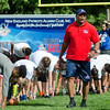 Derrick Beasley looks on as kids stretch before the New England Patriots Alumni Club's annual Football For You youth football clinic at Crocker Field on Thursday. SENTINEL & ENTERPRISE / Ashley Green