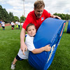 Former Patriots player Ilia Jarastchuk demonstrates a drill with Patrick Heffernan, 8, during the New England Patriots Alumni Club's annual Football For You youth football clinic at Crocker Field on Thursday. SENTINEL & ENTERPRISE / Ashley Green