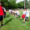 Former Patriots player Derrick Beasley works on a drill with kids during the New England Patriots Alumni Club's annual Football For You youth football clinic at Crocker Field on Thursday. SENTINEL & ENTERPRISE / Ashley Green