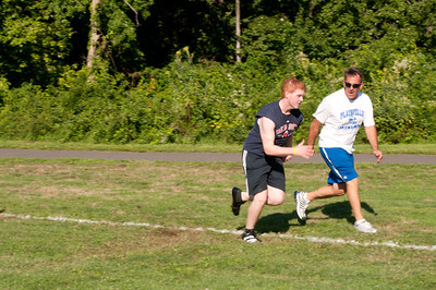 A player gets encouragemant from a coach while runing a dril at practice.