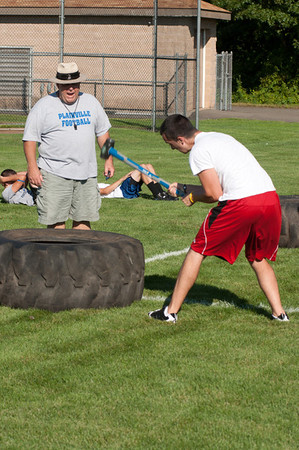 A player attacks a tire with a sledgehammer during practice with a coach looking on.