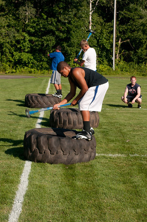 3 players work on endurance by hitting tires with sledgehammers