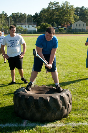 A player swings a sledgehammer at football practice.