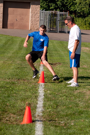A player runs a sprint drill at practice with a coach watching.