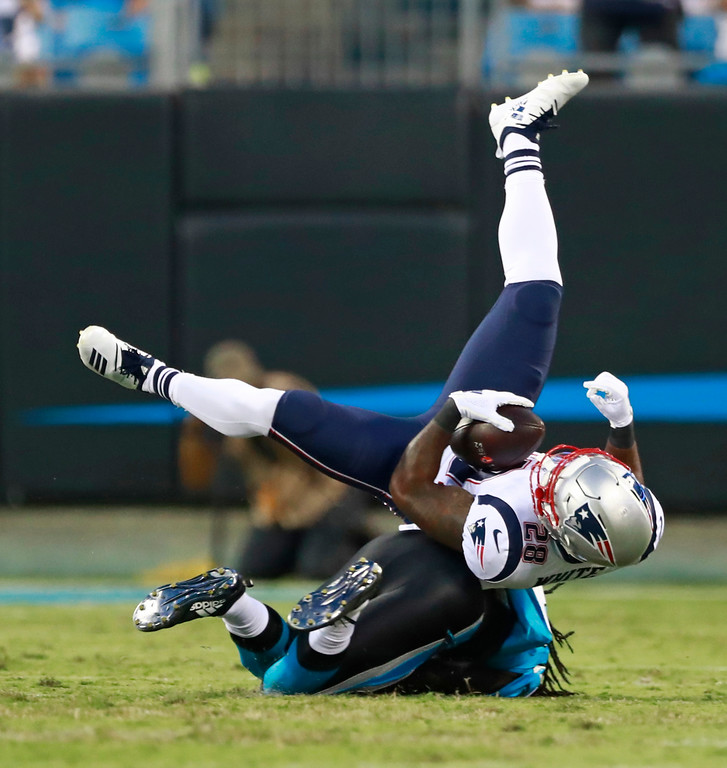 . New England Patriots\' James White (28) is upended by a Carolina Panthers player after a catch during the first half of a preseason NFL football game in Charlotte, N.C., Friday, Aug. 24, 2018. (AP Photo/Jason E. Miczek)