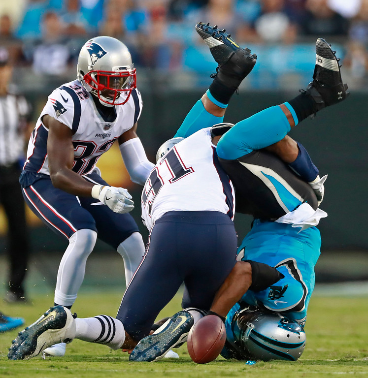 . Carolina Panthers\' Cam Newton, right, fumbles the ball as he lands on his head after being hit by New England Patriots\' Deatrich Wise (91) during the first half of a preseason NFL football game in Charlotte, N.C., Friday, Aug. 24, 2018. The Panthers recovered the ball. (AP Photo/Jason E. Miczek)