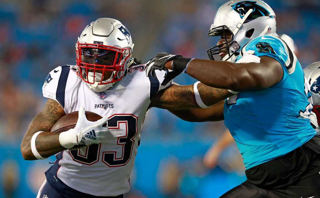 . New England Patriots\' Jeremy Hill (33) is tackled by Carolina Panthers\' Sterling Bailey (79) during the second half of a preseason NFL football game in Charlotte, N.C., Friday, Aug. 24, 2018. (AP Photo/Jason E. Miczek)