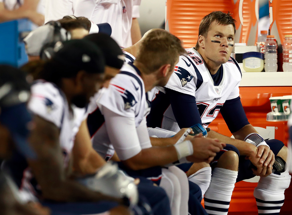 . New England Patriots\' Tom Brady (12) watches from the bench with teammates during the second half of a preseason NFL football game against the Carolina Panthers in Charlotte, N.C., Friday, Aug. 24, 2018. (AP Photo/Jason E. Miczek)
