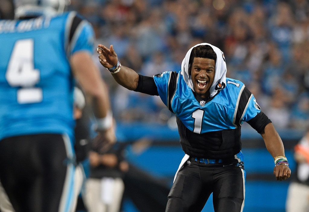 . Carolina Panthers\' Cam Newton (1) celebrates from the sidelines after a play against the New England Patriots during the second half of a preseason NFL football game in Charlotte, N.C., Friday, Aug. 24, 2018. (AP Photo/Mike McCarn)