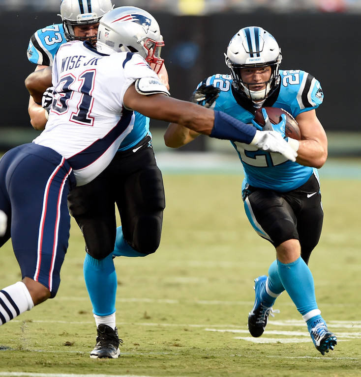 . Carolina Panthers\' Christian McCaffrey (22) runs as New England Patriots\' Deatrich Wise (91) defends during the first half of a preseason NFL football game in Charlotte, N.C., Friday, Aug. 24, 2018. (AP Photo/Mike McCarn)