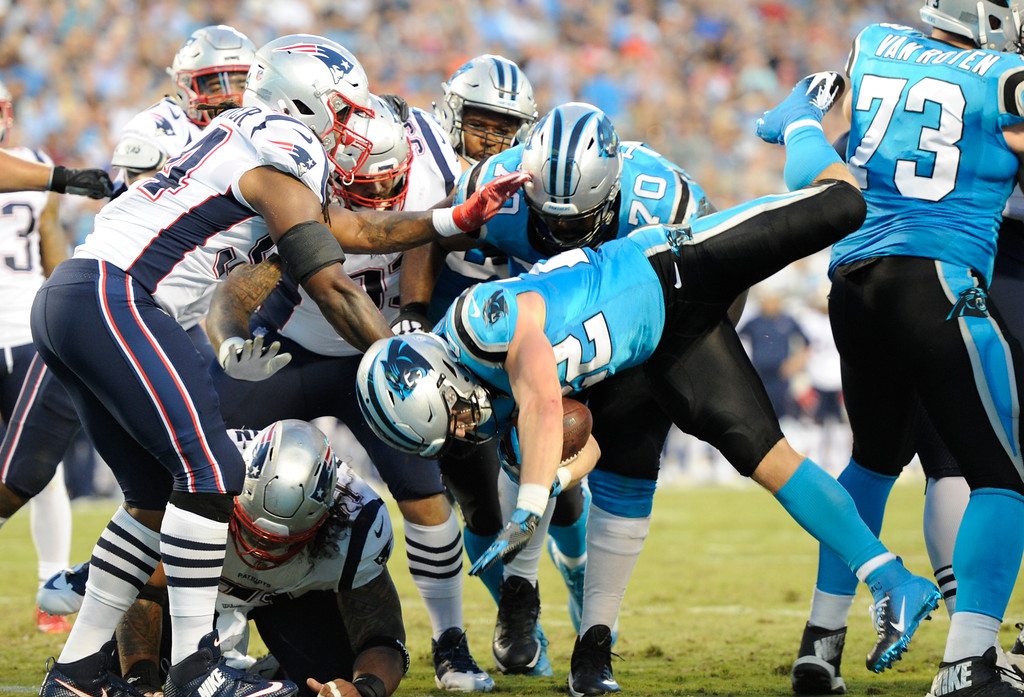 . Carolina Panthers\' Christian McCaffrey (22) dives as New England Patriots\' Dont\'a Hightower (54) defends during the first half of a preseason NFL football game in Charlotte, N.C., Friday, Aug. 24, 2018. (AP Photo/Mike McCarn)