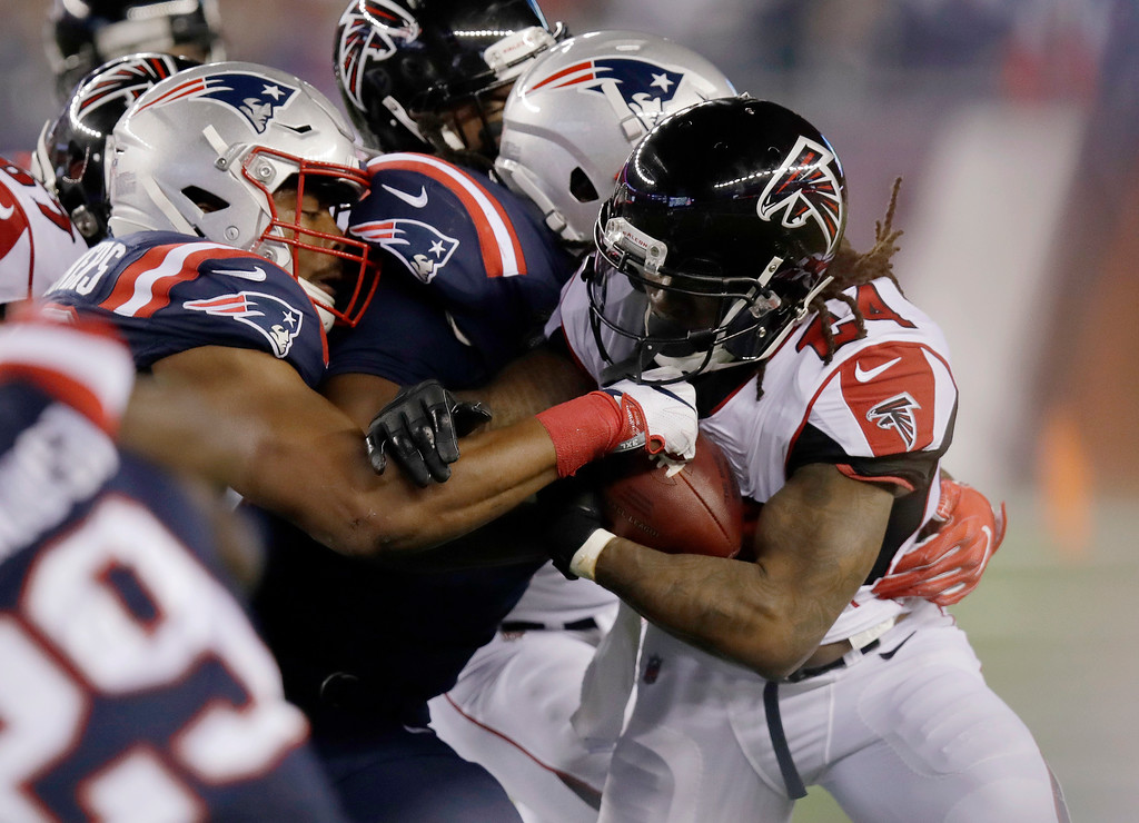 . New England Patriots defenders stop Atlanta Falcons running back Devonta Freeman (24) during the first half of an NFL football game, Sunday, Oct. 22, 2017, in Foxborough, Mass. (AP Photo/Charles Krupa)