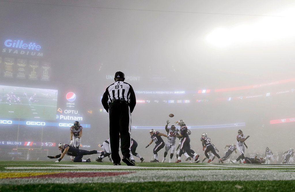 . New England Patriots quarterback Tom Brady, center, passes in the fog against the Atlanta Falcons during the second half of an NFL football game, Sunday, Oct. 22, 2017, in Foxborough, Mass. (AP Photo/Charles Krupa)