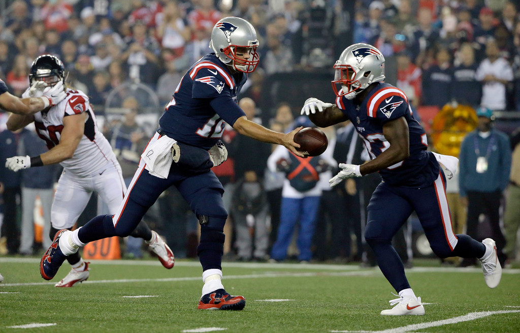 . New England Patriots quarterback Tom Brady, left, hands off to running back Dion Lewis during the first half of an NFL football game against the Atlanta Falcons, Sunday, Oct. 22, 2017, in Foxborough, Mass. (AP Photo/Steven Senne)