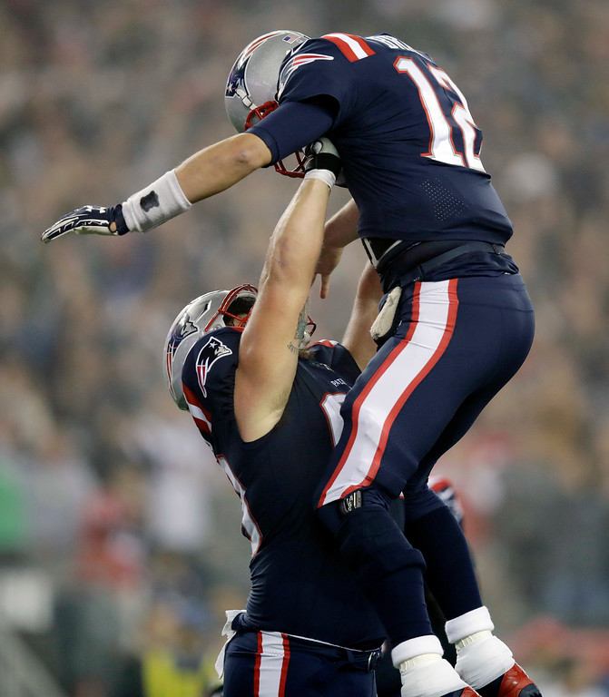 . New England Patriots quarterback Tom Brady gets a lift from center David Andrews to celebrate his touchdown pass to James White during the first half of an NFL football game against the Atlanta Falcons, Sunday, Oct. 22, 2017, in Foxborough, Mass. (AP Photo/Charles Krupa)