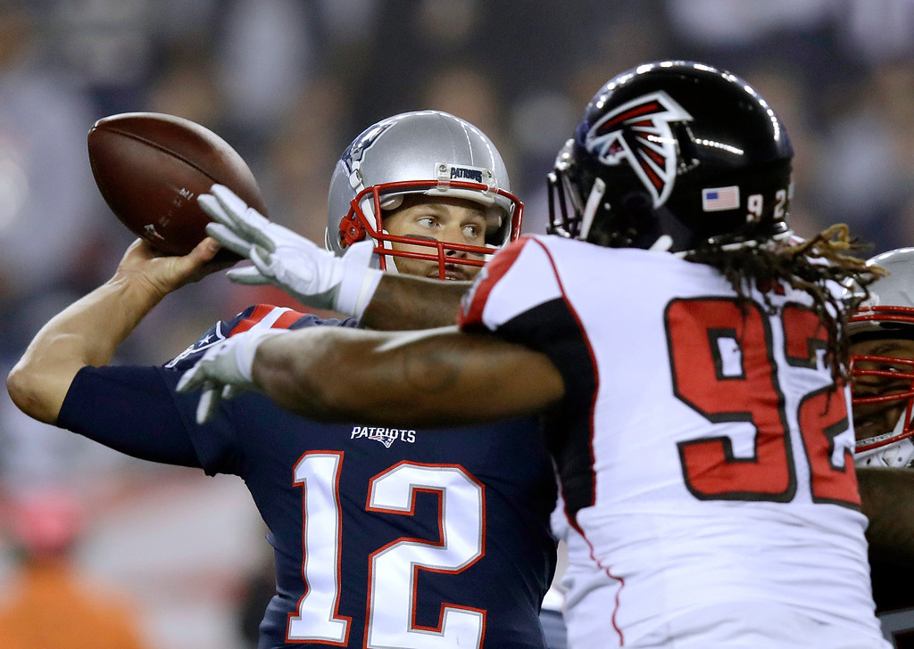 . New England Patriots quarterback Tom Brady, left, passes under pressure from Atlanta Falcons defensive tackle Dontari Poe (92) during the first half of an NFL football game, Sunday, Oct. 22, 2017, in Foxborough, Mass. (AP Photo/Charles Krupa)