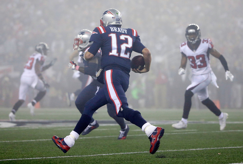. New England Patriots quarterback Tom Brady (12) runs in the fog as Atlanta Falcons defensive back Blidi Wreh-Wilson (33) pursues during the second half of an NFL football game, Sunday, Oct. 22, 2017, in Foxborough, Mass. (AP Photo/Steven Senne)