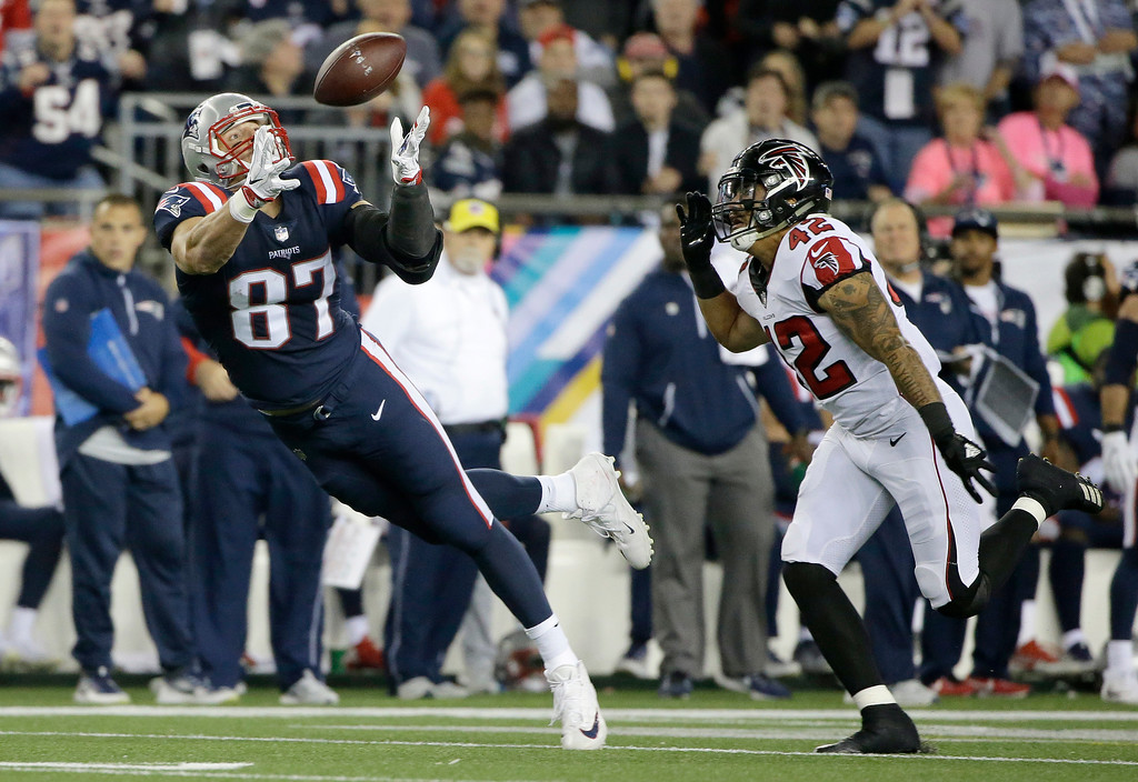 . New England Patriots tight end Rob Gronkowski (87) catches a pass in front of Atlanta Falcons linebacker Duke Riley (42) during the first half of an NFL football game, Sunday, Oct. 22, 2017, in Foxborough, Mass. The play was nullified on an offensive pass interference penalty by Gronkowski. (AP Photo/Steven Senne)