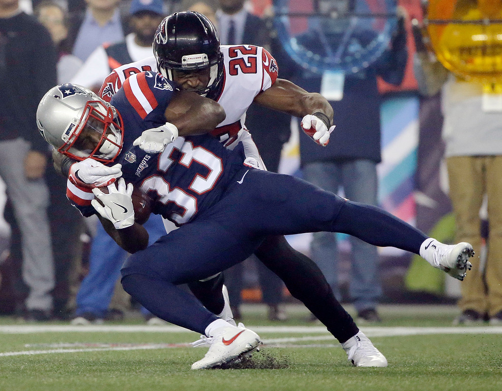. Atlanta Falcons safety Keanu Neal, rear, tackles New England Patriots running back Dion Lewis (33) during the first half of an NFL football game, Sunday, Oct. 22, 2017, in Foxborough, Mass. (AP Photo/Steven Senne)