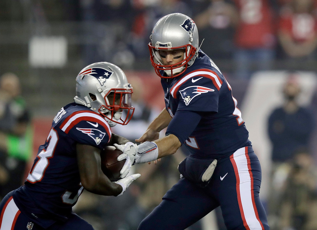 . New England Patriots quarterback Tom Brady, right, hands off to running back Dion Lewis during the first half of an NFL football game against the Atlanta Falcons, Sunday, Oct. 22, 2017, in Foxborough, Mass. (AP Photo/Charles Krupa)