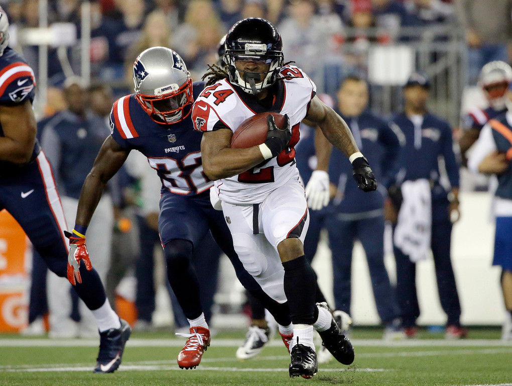 . Atlanta Falcons running back Devonta Freeman (24) runs from New England Patriots safety Devin McCourty (32) during the first half of an NFL football game, Sunday, Oct. 22, 2017, in Foxborough, Mass. (AP Photo/Steven Senne)