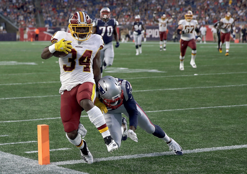 . Washington Redskins running back Byron Marshall (34) scores a touchdown in front of New England Patriots defensive back Duron Harmon (21) during the first half of a preseason NFL football game, Thursday, Aug. 9, 2018, in Foxborough, Mass. (AP Photo/Charles Krupa)
