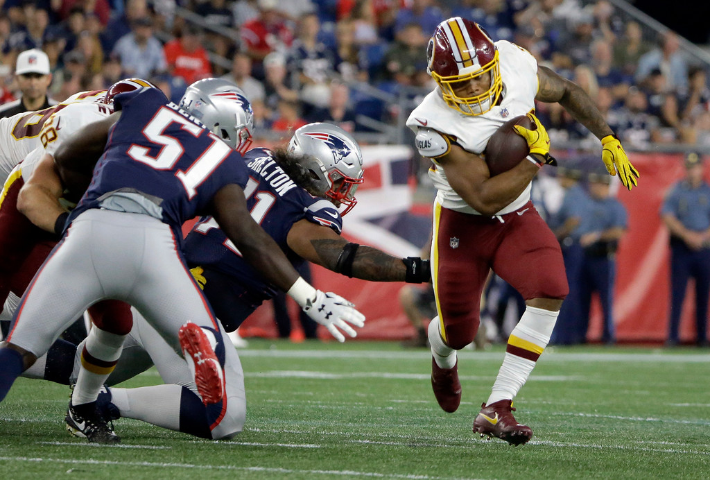. Washington Redskins running back Derrius Guice, right, evades New England Patriots linebacker Ja\'Whaun Bentley (51) and defensive tackle Danny Shelton, center, during the first half of a preseason NFL football game, Thursday, Aug. 9, 2018, in Foxborough, Mass. (AP Photo/Steven Senne)