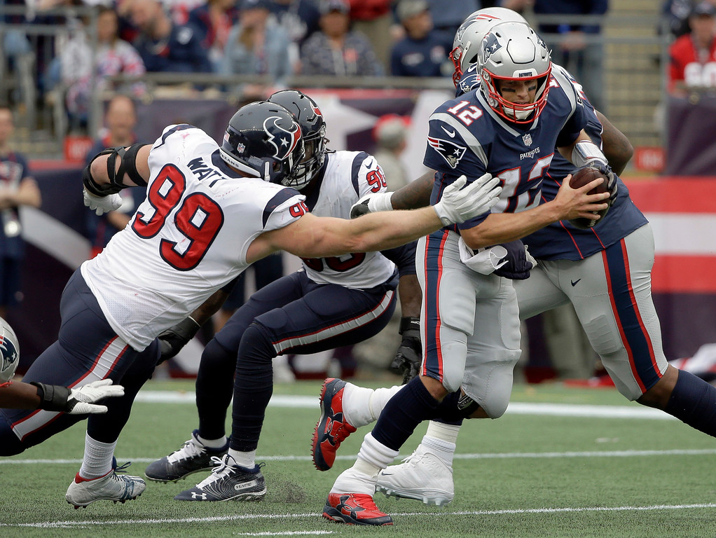 . Houston Texans defensive end J.J. Watt (99) tries to pull down New England Patriots quarterback Tom Brady (12) during the second half of an NFL football game, Sunday, Sept. 9, 2018, in Foxborough, Mass. (AP Photo/Steven Senne)