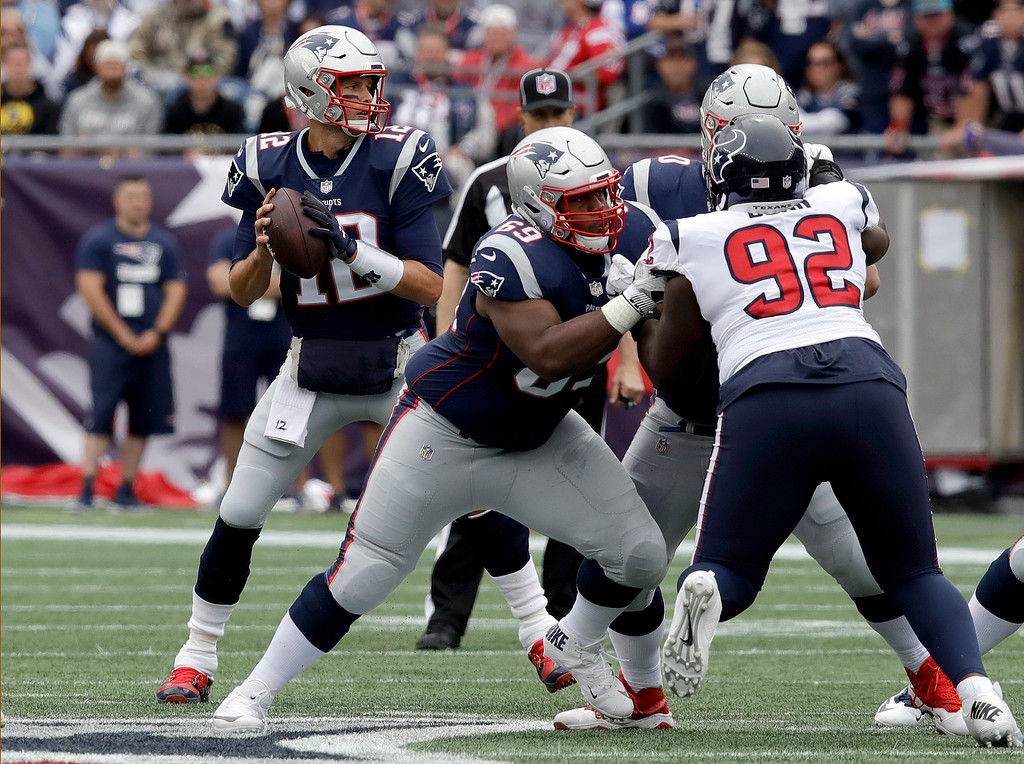 . New England Patriots quarterback Tom Brady, left, looks for a receiver under pressure from Houston Texans defensive tackle Brandon Dunn (92) during the first half of an NFL football game, Sunday, Sept. 9, 2018, in Foxborough, Mass. (AP Photo/Charles Krupa)