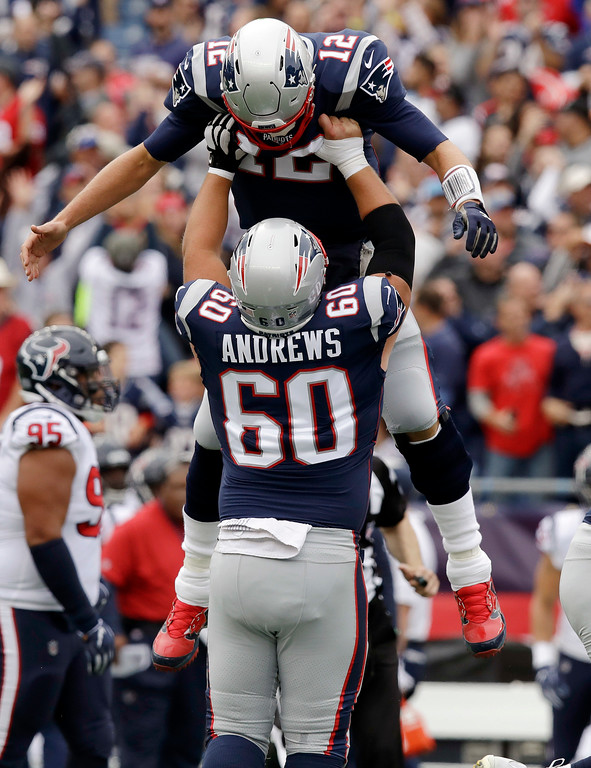 . New England Patriots quarterback Tom Brady (12) gets a lift from center David Andrews after throwing a touchdown pass to Rob Gronkowski during the first half of an NFL football game against the Houston Texans, Sunday, Sept. 9, 2018, in Foxborough, Mass. (AP Photo/Charles Krupa)