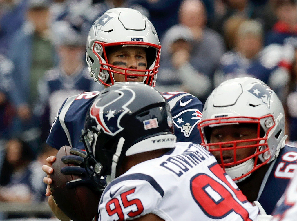 . New England Patriots quarterback Tom Brady, rear, looks for a receiver under pressure from Houston Texans defensive end Christian Covington (95) during the first half of an NFL football game, Sunday, Sept. 9, 2018, in Foxborough, Mass. The Patriots won, 27-20. (AP Photo/Charles Krupa)