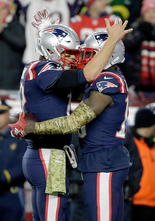 . New England Patriots quarterback Tom Brady, left, celebrates his touchdown pass to wide receiver Josh Gordon, right, during the second half of an NFL football game against the Green Bay Packers, Sunday, Nov. 4, 2018, in Foxborough, Mass. (AP Photo/Steven Senne)