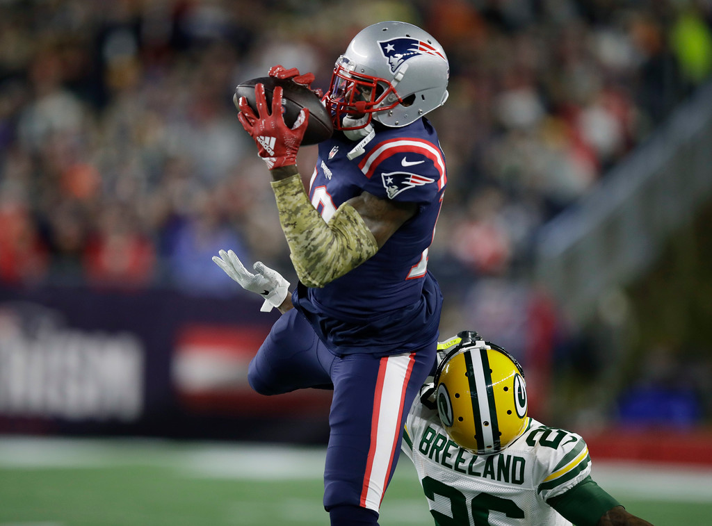 . New England Patriots wide receiver Josh Gordon catches a pass as Green Bay Packers defensive back Bashaud Breeland, right, defends during the first half of an NFL football game, Sunday, Nov. 4, 2018, in Foxborough, Mass. (AP Photo/Charles Krupa)