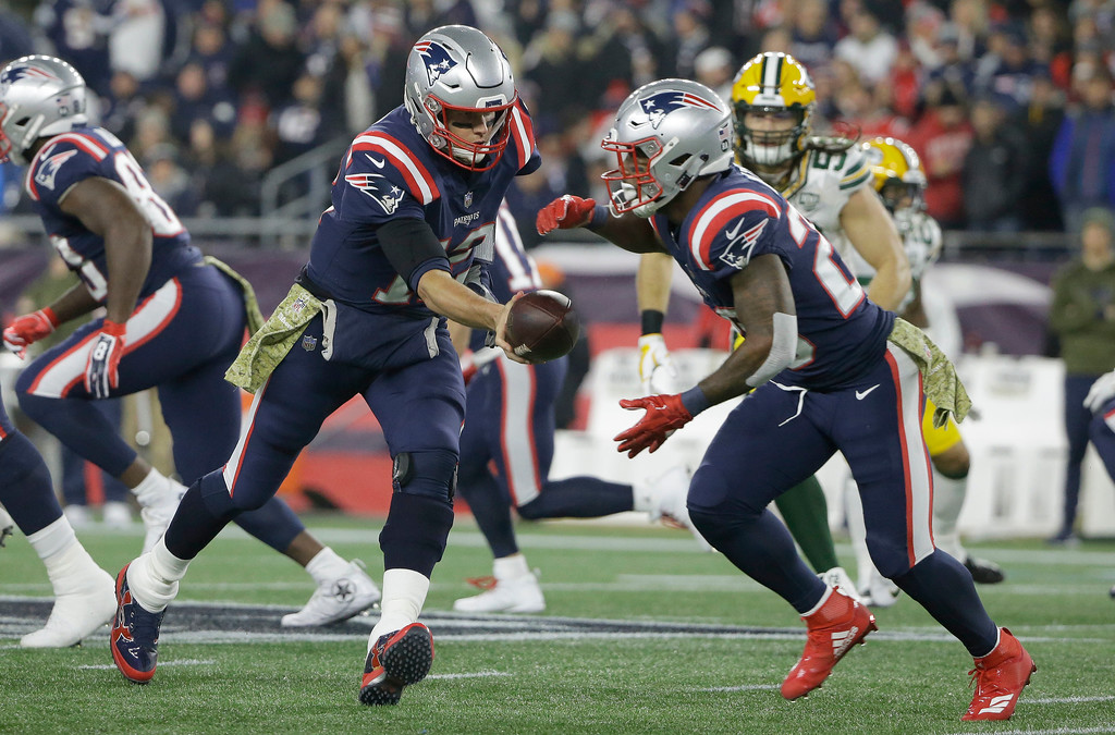 . New England Patriots quarterback Tom Brady, left, hands off to running back James White during the first half of an NFL football game against the Green Bay Packers, Sunday, Nov. 4, 2018, in Foxborough, Mass. (AP Photo/Steven Senne)