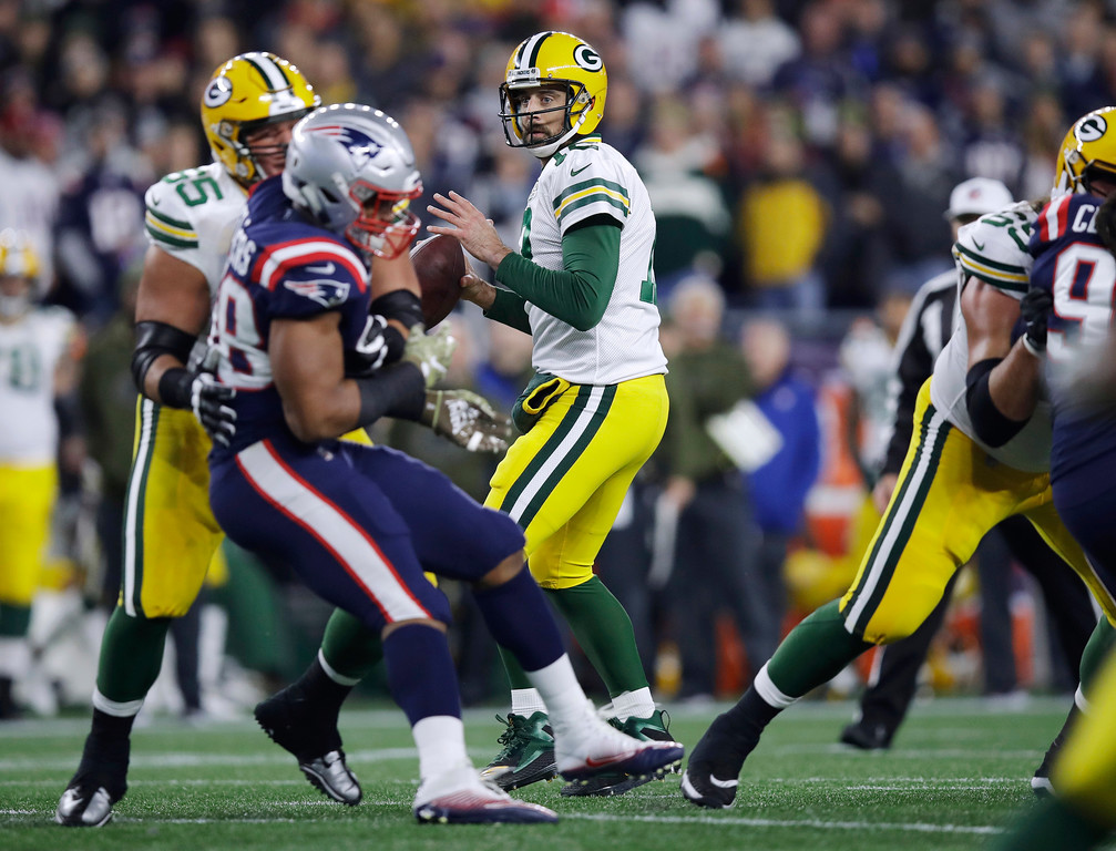 . Green Bay Packers quarterback Aaron Rodgers, center, looks for a receiver under pressure from the New England Patriots during the first half of an NFL football game, Sunday, Nov. 4, 2018, in Foxborough, Mass. (AP Photo/Charles Krupa)