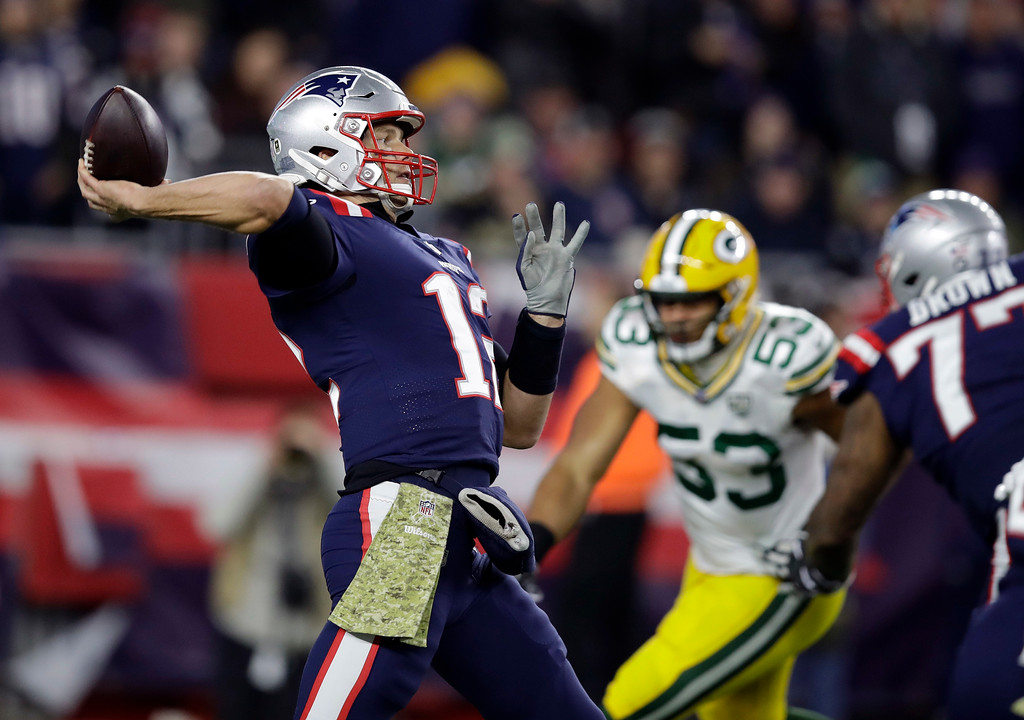 . New England Patriots quarterback Tom Brady, left, passes under pressure from Green Bay Packers outside linebacker Nick Perry (53) during the first half of an NFL football game, Sunday, Nov. 4, 2018, in Foxborough, Mass. (AP Photo/Charles Krupa)