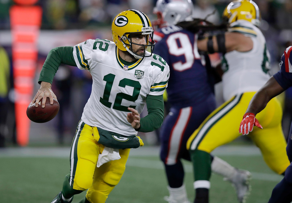. Green Bay Packers quarterback Aaron Rodgers (12) scrambles against the New England Patriots during the first half of an NFL football game, Sunday, Nov. 4, 2018, in Foxborough, Mass. (AP Photo/Charles Krupa)