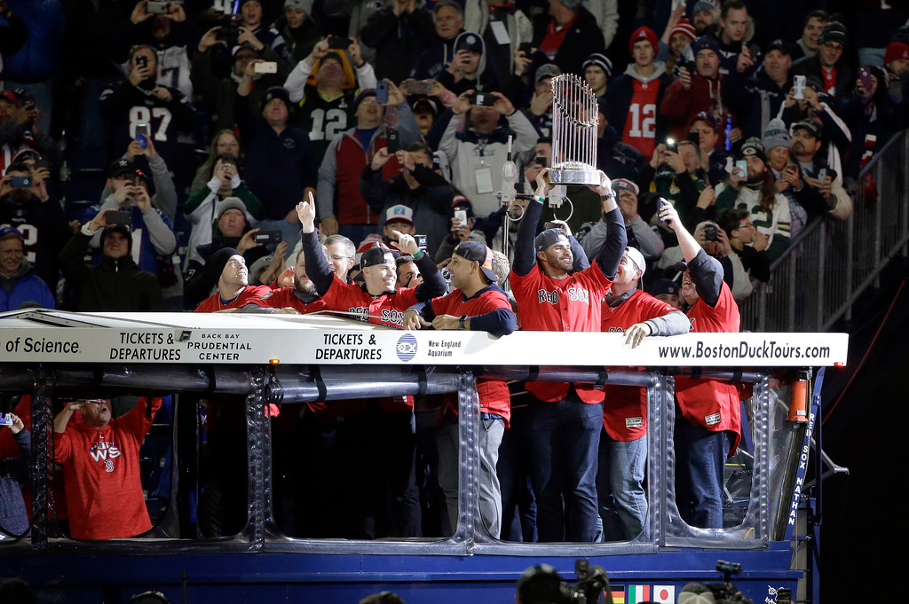 . Boston Red Sox\'s J.D. Martinez holds the World Series trophy as he and other Red Sox players ride onto the field in a duckboat before an NFL football game between the New England Patriots and the Green Bay Packers, Sunday, Nov. 4, 2018, in Foxborough, Mass. (AP Photo/Steven Senne)