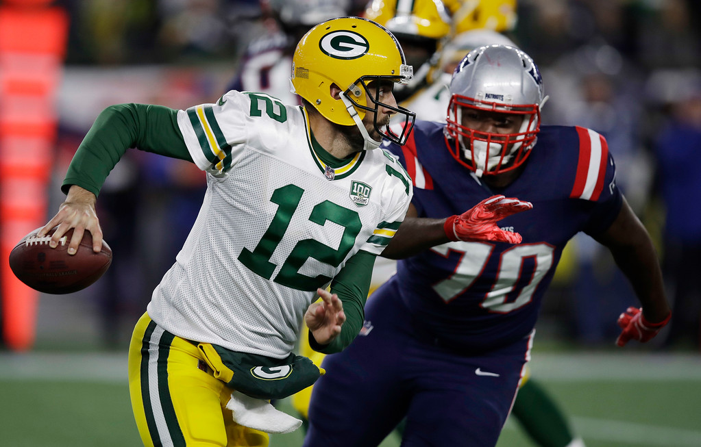 . Green Bay Packers quarterback Aaron Rodgers, left, runs from New England Patriots defensive tackle Adam Butler (70) during the first half of an NFL football game, Sunday, Nov. 4, 2018, in Foxborough, Mass. (AP Photo/Charles Krupa)