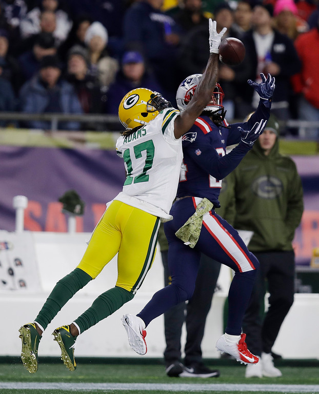 . Green Bay Packers wide receiver Davante Adams (17) and New England Patriots defensive back Stephon Gilmore, right, reach for a pass during the first half of an NFL football game, Sunday, Nov. 4, 2018, in Foxborough, Mass. The pass was incomplete. (AP Photo/Charles Krupa)