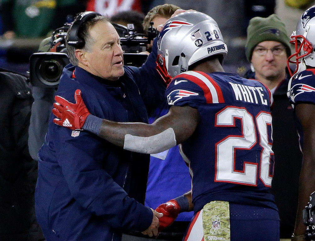 . New England Patriots head coach Bill Belichick, left, congratulates running back James White on his touchdown during the second half of an NFL football game against the Green Bay Packers, Sunday, Nov. 4, 2018, in Foxborough, Mass. (AP Photo/Steven Senne)