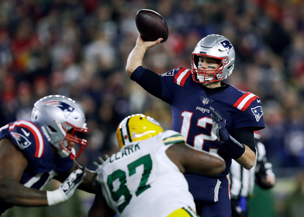 . New England Patriots quarterback Tom Brady (12) passes under pressure from Green Bay Packers nose tackle Kenny Clark (97) during the first half of an NFL football game, Sunday, Nov. 4, 2018, in Foxborough, Mass. (AP Photo/Charles Krupa)