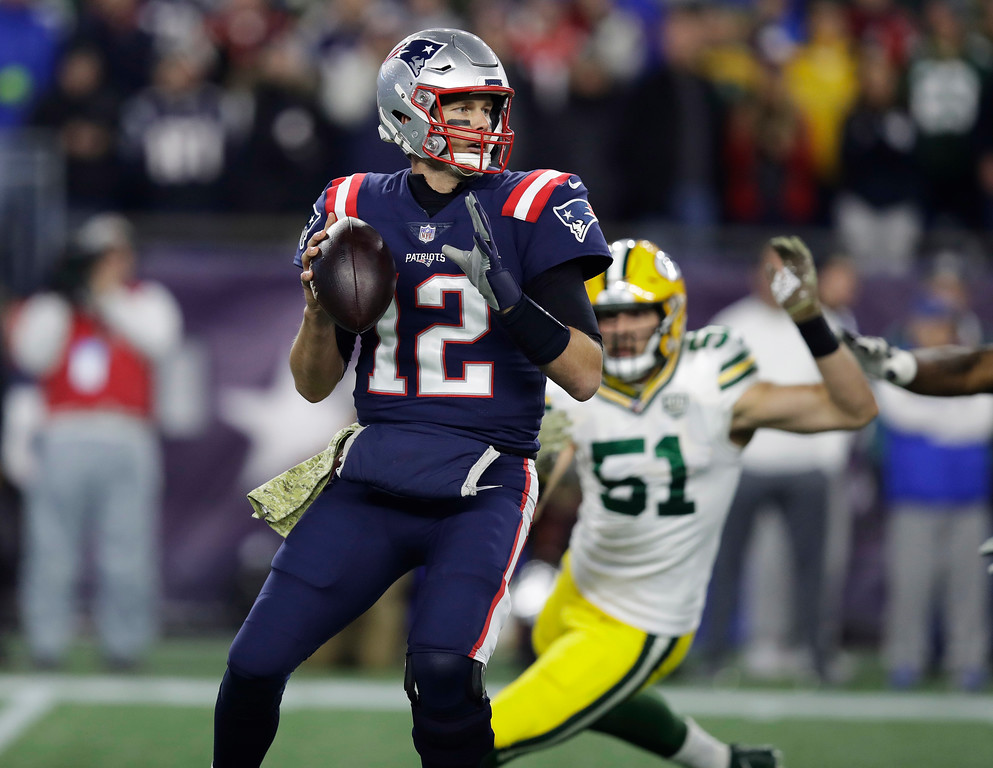 . New England Patriots quarterback Tom Brady (12) passes under pressure from Green Bay Packers linebacker Kyler Fackrell (51) during the first half of an NFL football game, Sunday, Nov. 4, 2018, in Foxborough, Mass. (AP Photo/Charles Krupa)