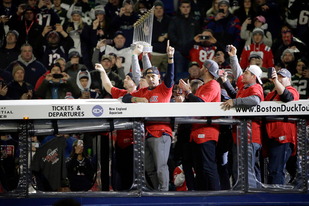 . Boston Red Sox manager Alex Cora, front left, rides onto the field in a duckboat with the World Series trophy and Red Sox players before an NFL football game between the New England Patriots and the Green Bay Packers, Sunday, Nov. 4, 2018, in Foxborough, Mass. (AP Photo/Steven Senne)